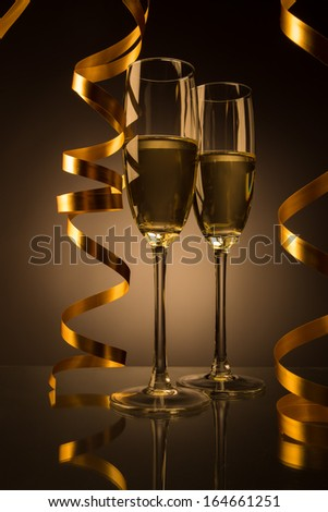 Two glasses of champagne on yellow, gold background - stock photo