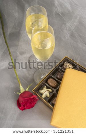 Two Glasses of Champagne, Single Red Rose and Box of Decadent Chocolates for Valentines Day - stock photo