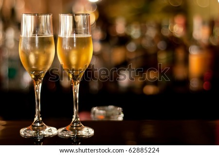 Two glasses of champagne waiting to be served by guests in a restaurant, new year's eve. - stock photo
