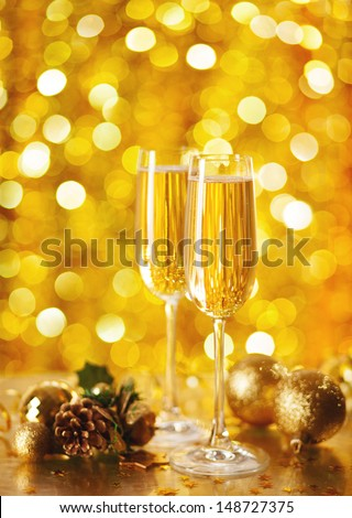 Two glasses of champagne with a Christmas decor in the background. selective focus.  very shallow depth of field, focus on near glass.