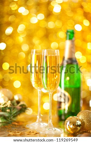Two glasses of champagne with a Christmas decor in the background. very shallow depth of field, focus on near glass.