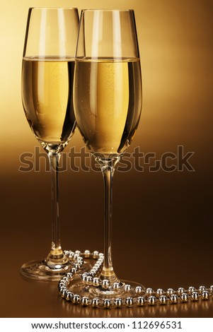 two glasses of champagne with a silver chain on golden background - stock photo