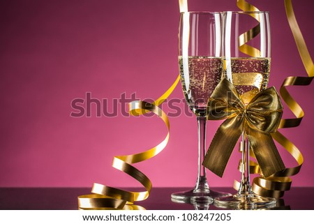 Two glasses of champagne with bow on pink background - stock photo