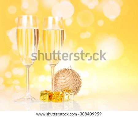 Two glasses of champagne with christmas decorations on yellow background - stock photo