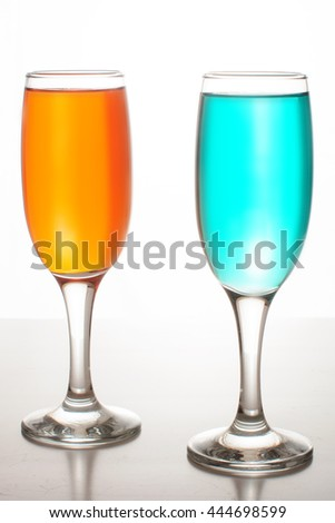 two glasses of champagne with colored liquids on white background