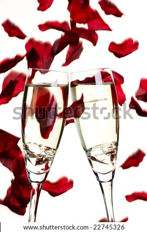 Two glasses of champagne with diamonds with falling rose petals in background - stock photo