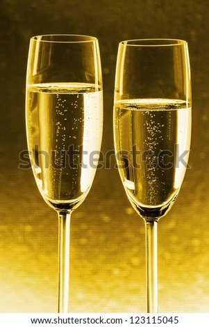 Two glasses of champagne with gold background