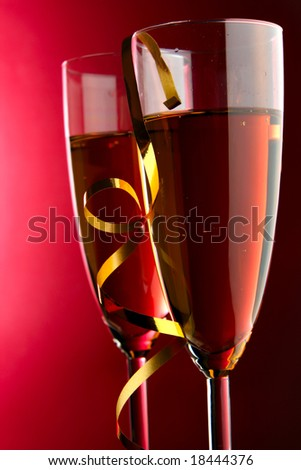 Two glasses of champagne with gold streamer over red background - stock photo