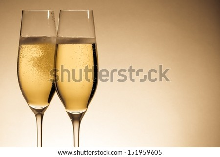 two glasses of champagne with golden bubbles and space for text - stock photo