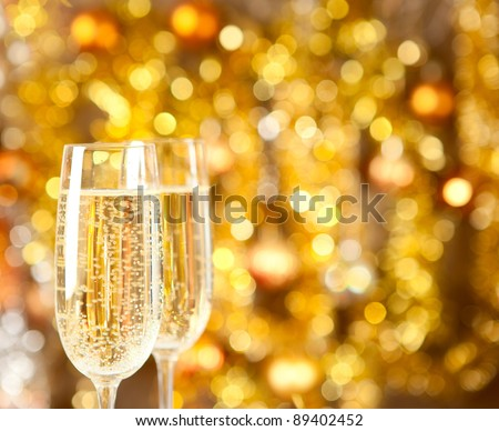Two glasses of champagne with lights in the background. very shallow depth of field, focus on near glass. - stock photo