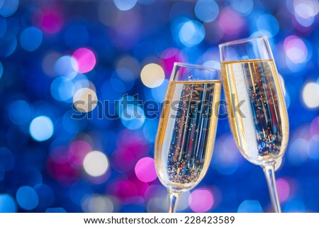 Two glasses of champagne with lights in the background. very shallow depth of field. Selective focus. - stock photo
