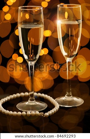 Two glasses of champagne with pearl necklace - stock photo
