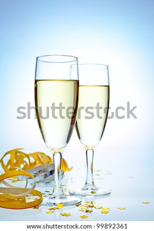 Two glasses of champagne with ribbons and confetti - stock photo