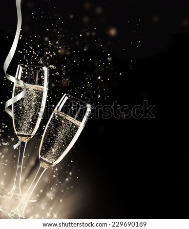 Two glasses of champagne with splash, on black background - stock photo