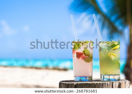 two glasses of chilled cocktail mohito and sunglasses on table near the beach - stock photo