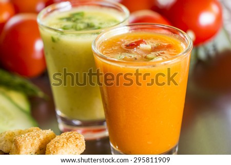 Two glasses of chilled gazpacho soup, one green and one orange, with fresh ripe cherry tomatoes and sliced cucumber ingredients - stock photo