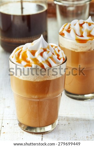 two glasses of coffee with whipped cream on white wooden table - stock photo