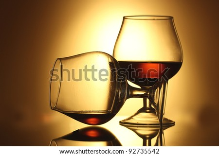 Two glasses of cognac on yellow background