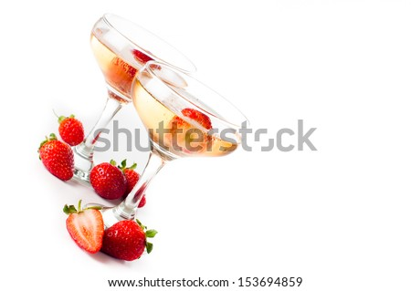 Two glasses of cold champagne with strawberries on a white background, isolated, close-up - stock photo