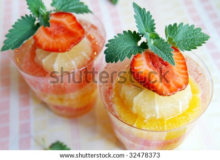 Two glasses of cooling citrus (lemon, orange, grapefruit) drink decorated with fresh strawberry and mint leaves, blur background, closeup - stock photo