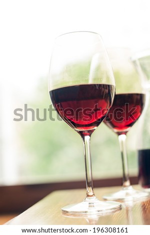 Two glasses of delicious red wine. Vintage filter. Indoors. - stock photo