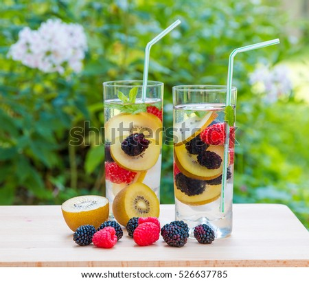 Two glasses of delicious refreshing drink. Infused water with berries,  golden kiwi and mint. Top view
