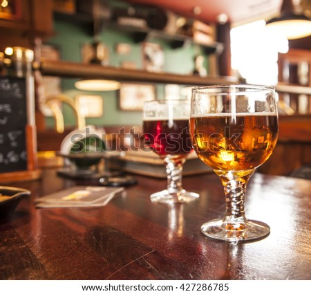 Two glasses of draught beer, a red and a amber beer - stock photo