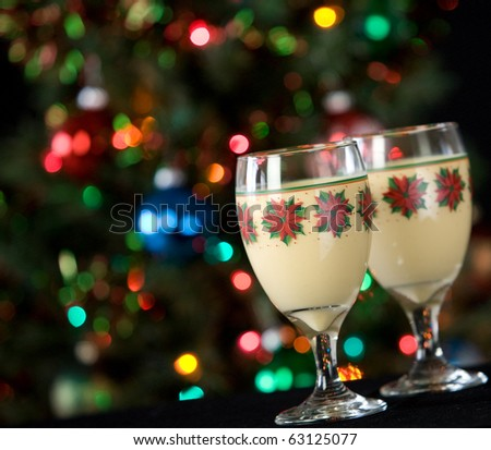 Two glasses of eggnog in festive holiday glasses in front of christmas tree with lights