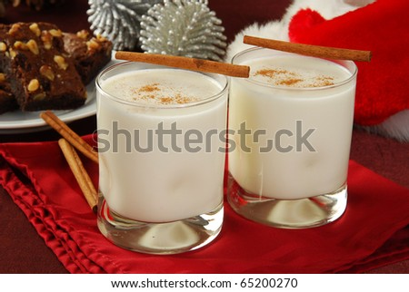 Two glasses of eggnog with brownies and a Santa hat in the background - stock photo