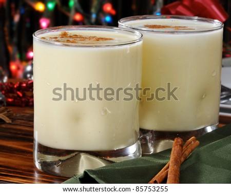 Two glasses of eggnog with cinnamon sticks near the Christmas tree - stock photo