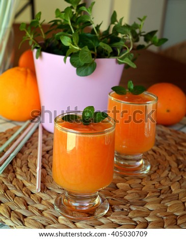Two glasses of fresh grapefruit,orange and papaya smoothie on a wooden table. Closeup.  - stock photo