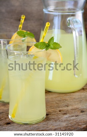 Two glasses of fresh lemonade garnished with lemon slices and mint leaves. Used a wood textured background for a rustic look. - stock photo