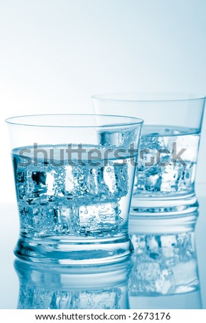 Two glasses of fresh water with cubes of ice in it over aqua colored background with copyspace