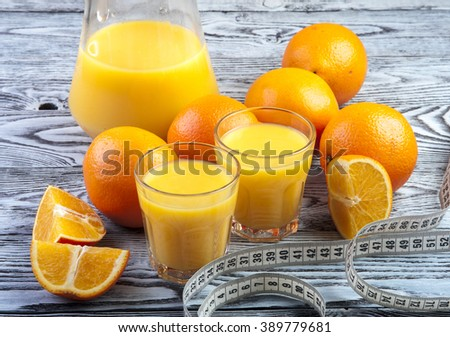Two glasses of freshly squeezed orange juice, ripe oranges and measuring tape. Healthy food for weight loss. - stock photo