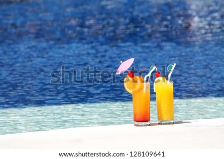 two glasses of fruit juice on blue water background - stock photo