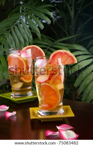 Two glasses of grapefruit and rose iced tea on a table in a restaurant on a tropical beach.