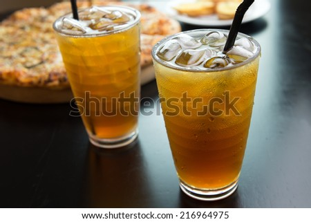 Two glasses of ice tea drink with pizza in the background - stock photo