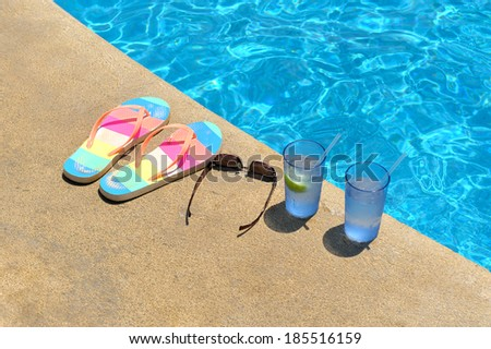 Two glasses of ice water, pear of sandals and women�s sunglasses - stock photo
