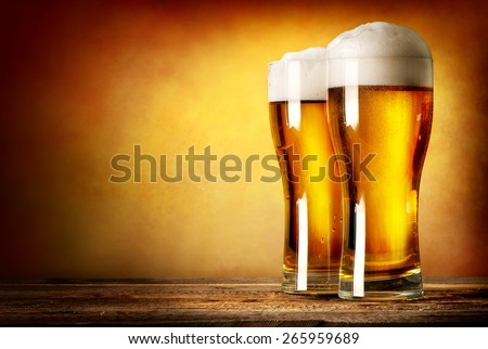 Two glasses of lager on a wooden table - stock photo