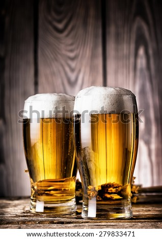 Two glasses of light beer with foam on a wooden background