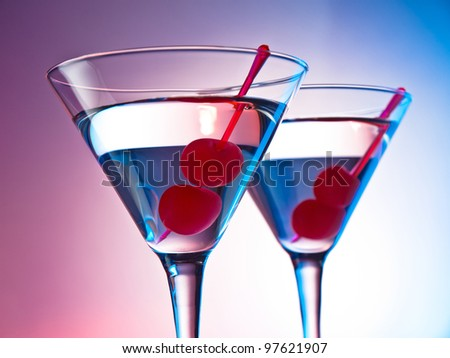Two glasses of martini with red cherries on a mixed color background - stock photo