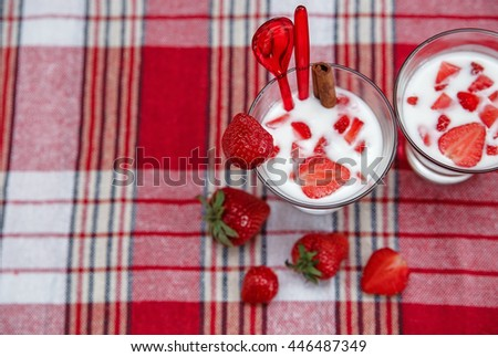 Two Glasses of Milk Cocktail,Red Fresh Strawberries with Plastic Spoons and Cinnamon on the Check Tablecloth.Breakfast.Cooking Vitamins Ingredients.Summer Fruits. - stock photo