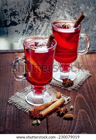 two glasses of mulled wine  on the old wooden table  in winter frosty day  - stock photo