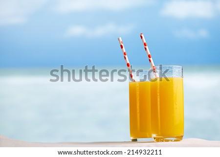 Two glasses of orange juice cocktail on white sandy beach - stock photo