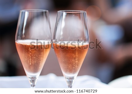 Two glasses of pink champagne for the couple. - stock photo