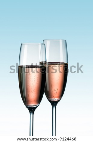 Two glasses of pink champagne on blue background
