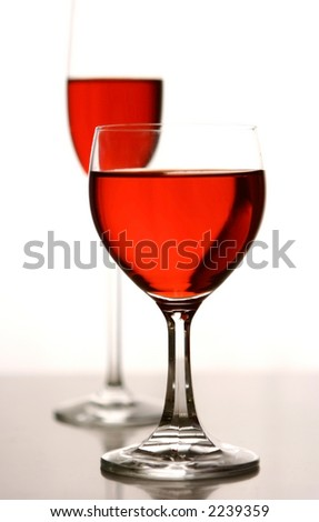 Two glasses of red concoction in glasses against white background lighting.