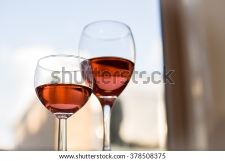 Two Glasses of Red Rose Wine with Brightly Lit Window Horizontal