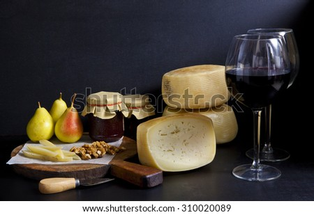 two glasses of red wine and cheese pecorino, pears jam. Parmesan cheese.Italian appetizer. still life. - stock photo