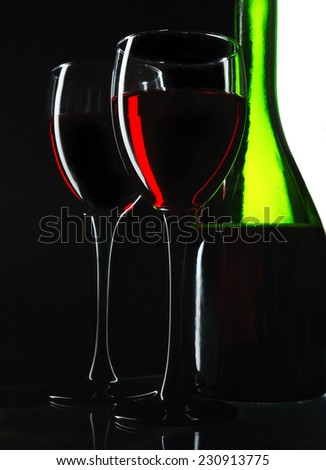 Two glasses of red wine and green bottle on black